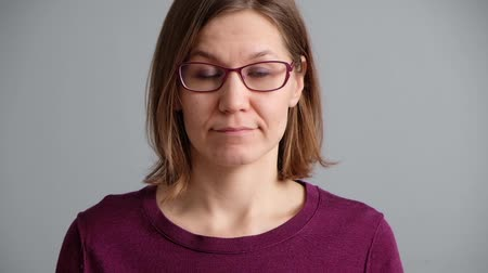 Pensive woman thinking and having an idea on gray background. Beautiful caucasian woman wearing sweater and glasses.
