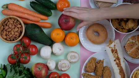 american cuisine : Concept shot of healthy and unhealthy food. Fruits and vegetables vs fast food. Somebodys hand choosing.