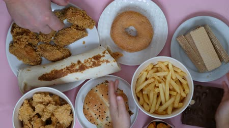 Unhealthy food concept. Fast food, burger, donut, french fries on a pink background. Hands taking food Стоковые видеозаписи