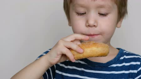 Little cute boy eating a donut . Fast food concept. Close up
