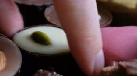 yermantarı : Woman chosing assorted chocolate from box tasty dessert background. Close up Stok Video