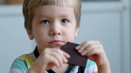 Cute boy eating chocolate, close up