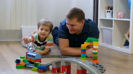 Family concept. Boy and dad playing with trains on wooden floor. Father with son Стоковые видеозаписи