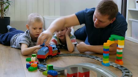 Family concept. Boys and dad playing with trains on wooden floor. Father with sons Стоковые видеозаписи