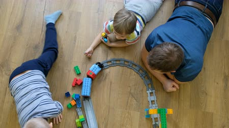 Family concept. Boys and dad playing with trains on wooden floor. Father with sons. Directly above view