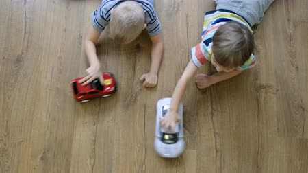 Family concept. Boys playing with cars on wooden floor. Directly above view