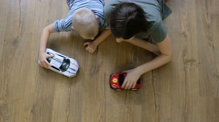 Family concept. Boys and mom playing with cars on wooden floor. Father with sons. Directly above view