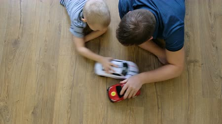 Family concept. Boy and dad playing with cars on wooden floor. Father with son. Directly above view