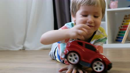 Cute little boy plays with toy car at home