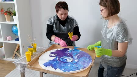 Women making fluid art acrylic painting. Creative cosmic artwork hippie wallpaper in blue color with hands of creator.