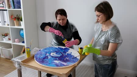 Women make fluid art acrylic painting. Creative cosmic artwork hippie wallpaper in blue color with hands of creator.