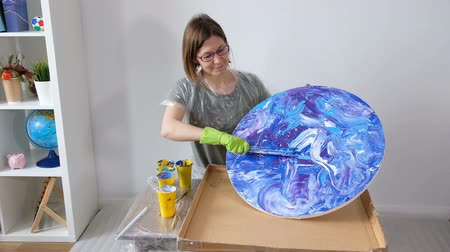 Woman make fluid art acrylic painting. Creative cosmic artwork hippie wallpaper in blue color with hands of creator.