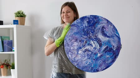 Woman with fluid art acrylic painting. Creative cosmic artwork hippie wallpaper in blue color with hands of creator.