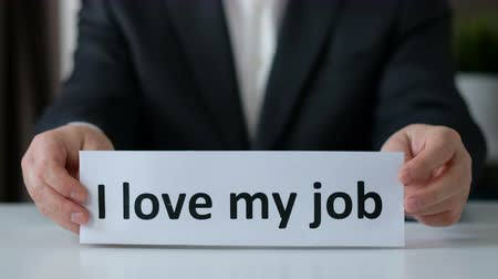 домашнее задание : I love my job concept. Business man hands holding a paper with the text. Close up Стоковые видеозаписи