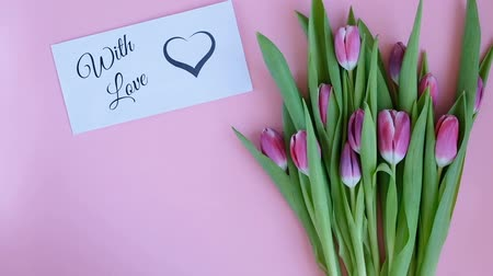 открытка : Tulips on pink background. Woman putting greeting card with the text WITH LOVE and a gift. Directly above view Стоковые видеозаписи