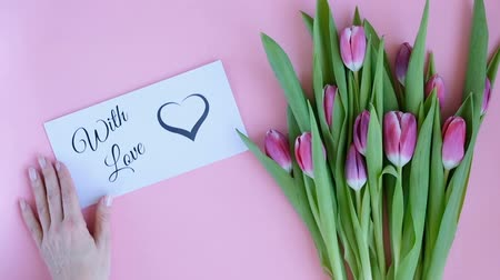 Tulips on pink background. Woman putting greeting card with the text WITH LOVE. Directly above view
