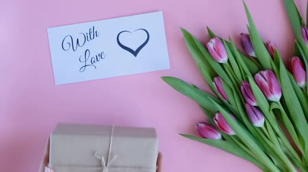 Tulips on pink background. Woman putting greeting card with the text WITH LOVE and a gift. Directly above view Wideo