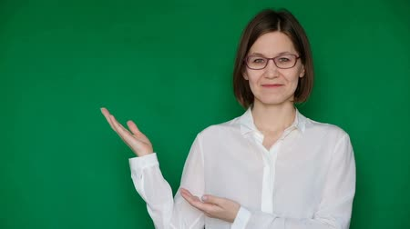 Beautiful smiling woman in glasses and white blouse pointing to the right on green screen, Chroma key