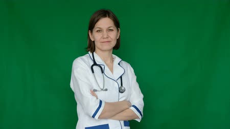 Smiling confident woman doctor in lab coat looking at the camera on a Green Screen, Chroma Key. Wideo