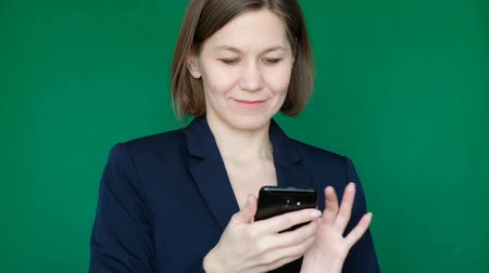 Woman working with smartphone on green background. Chroma Key. Close up Wideo