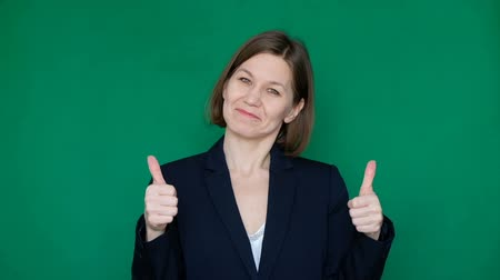 Confident business woman showinf thumb up, looking at camera and smiling on green background. Chroma key. Close up