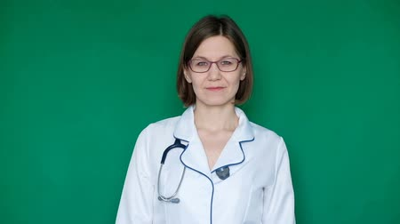 Smiling confident woman doctor in lab coat looking at the camera on a Green Screen, Chroma Key. Close up Wideo