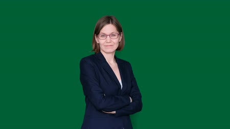 Confident business woman with crossed arms looking at camera and smiling on green background. Chroma key. Close up
