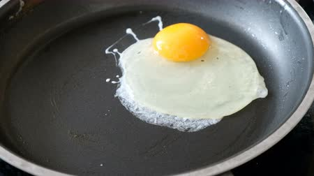 Somebody frying eggs on a pan, close up