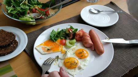 Man eating breakfast. Knife and fork in hand. American style breakfast with fried eggs, sausage, salad and toast. Wideo