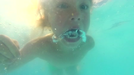 basen : Little blond girl with blue eyes dives underwater in a swimming pool. She is enjoying summer day and having fun. Sun is shining through water behind her