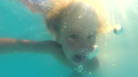 yüzme havuzu : Slow motion shot of little blond girl with blue eyes dives underwater in a swimming pool. She is enjoying summer day and having fun. Sun is shining through water behind her Stok Video