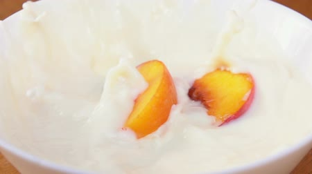 brzoskwinia : Slices of juicy peaches falling into the cream