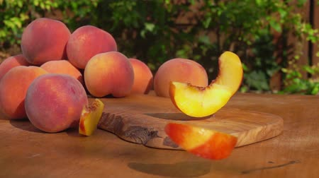 şeftali : Slices of juicy peaches falling on the wooden table Stok Video