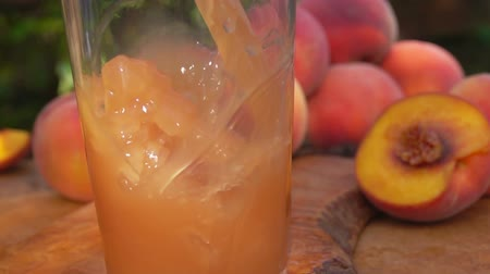 şeftali : Peach juice is poured into a glass, background of peaches Stok Video