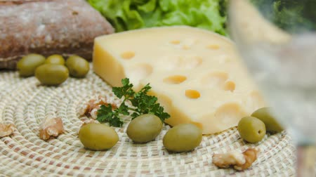 borgonha : White wine is poured into a glass on a background of Maasdam cheese with olives and nuts
