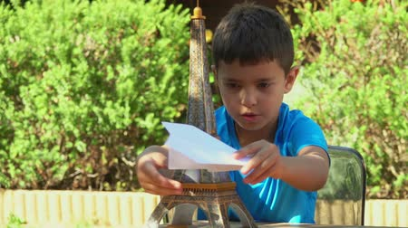 paper airplane : Boy playing with a paper airplane on a background model of the Eiffel Tower Stock Footage