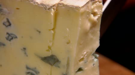 cheese piece : Close up of blue cheese cut on the background of a burning fireplace