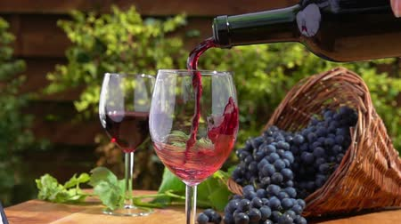 kırmızı şarap : Wine from the bottle is poured into a glass on a background of a basket of ripe grapes