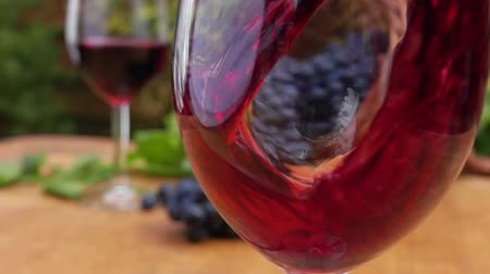 kırmızı şarap : Super close up red wine is poured into a glass on a wooden table, slow motion