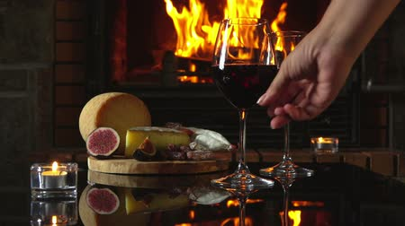 alcohol : Hand puts on the table a glass of red wine. Reflection of the fire in the fireplace glass table with wine and snacks