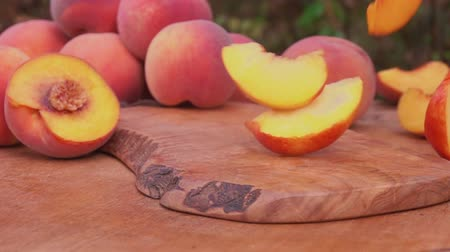 nektarinka : Peach slices falling on the wooden board Dostupné videozáznamy