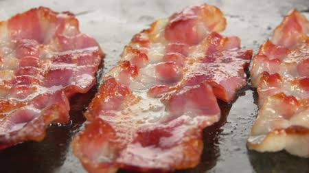 cozinhado : Fork corrects a slice of bacon on the hot surface of the stone grill