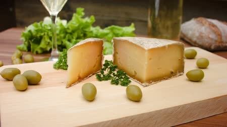 desszertek : Unpasteurised, semi-hard cheese made from sheeps milk with natural, crusty, brownish rind on a wooden board with herbs on background Stock mozgókép