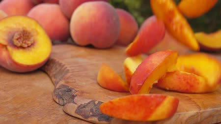 nektarinka : Slices of juicy peaches falling on the wooden table Dostupné videozáznamy