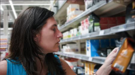 marca : Woman chooses food in the supermarket