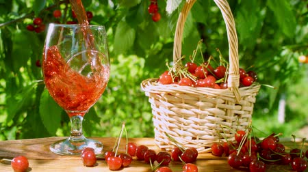ягоды : Beautiful fresh, ripe, juicy red cherry cherries in wicker basket on the wooden table. Cherry juice poured in to glass Стоковые видеозаписи