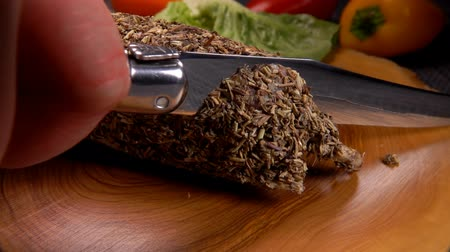 вылеченный : knife cuts off a piece of smoked spicy sausage on a wooden board very close-up Стоковые видеозаписи