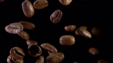 brew coffee : Fried coffee beans bouncing against to the camera on a dark background. Slow-motion shooting, very close-up