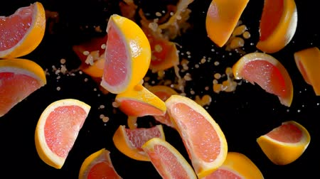 grejpfrut : Slices of grapefruit with juise bouncing against to the camera on a black background in slow motion