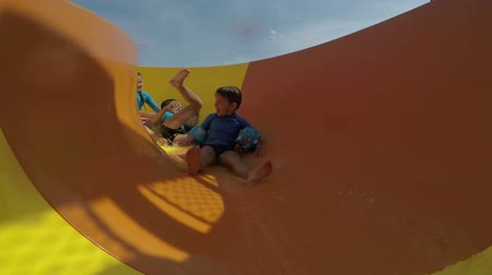 aqua park : Funny little boys and girls roll with yellow water slides Stock Footage